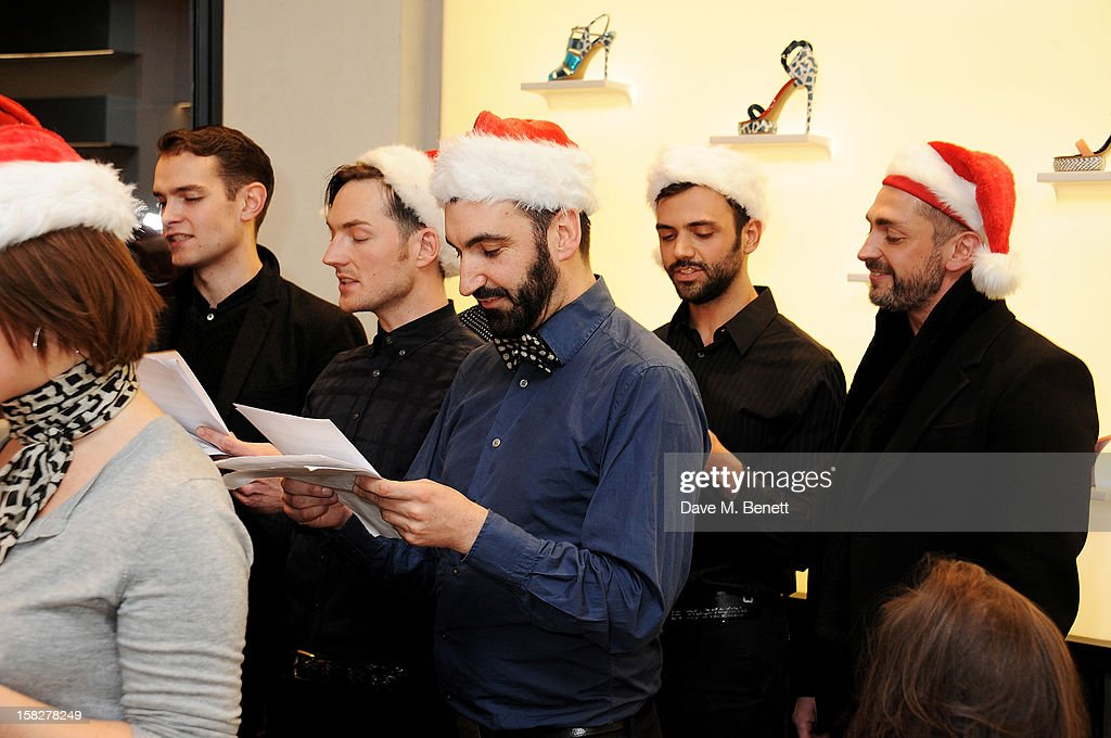 Dan Gillespie Sells (2L) and David Waddington (R) perform with The Bistotheque Choir at a Christmas drinks hosted by designer Nicholas Kirkwood to celebrate his partnership with Chambord black raspberry liquer, and launch the limited edition shoe 'The Chambord' at the Nicholas Kirkwood Mount Street store on December 12, 2012 in London, England.