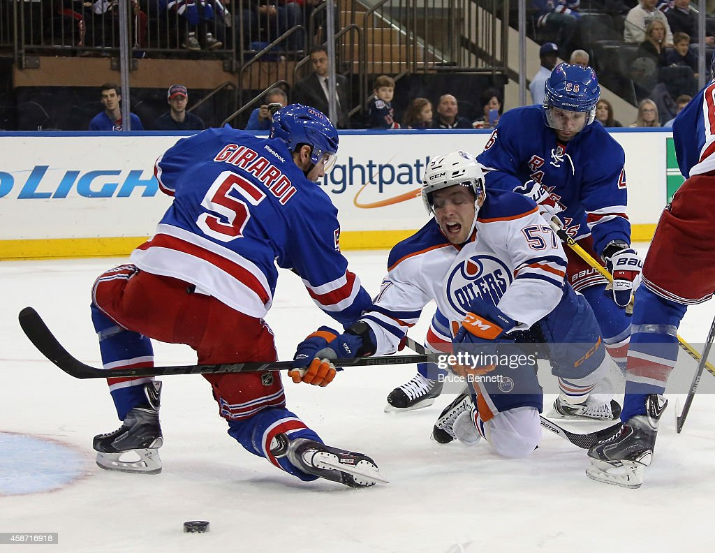 Dan Girardi and Martin St Louis of the New York Rangers defend against David Perron of the Edmonton Oilers during the first period at Madison Square...