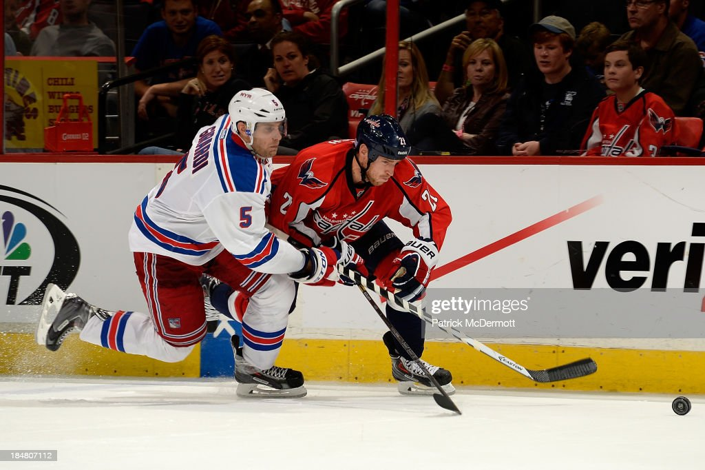 Dan Girardi #5 of the New York Rangers and <a gi-track='captionPersonalityLinkClicked' href=/galleries/search?phrase=Brooks+Laich&family=editorial&specificpeople=554432 ng-click='$event.stopPropagation()'>Brooks Laich</a> #21 of the Washington Capitals chase after the puck in the third period of an NHL game at Verizon Center on October 16, 2013 in Washington, DC.