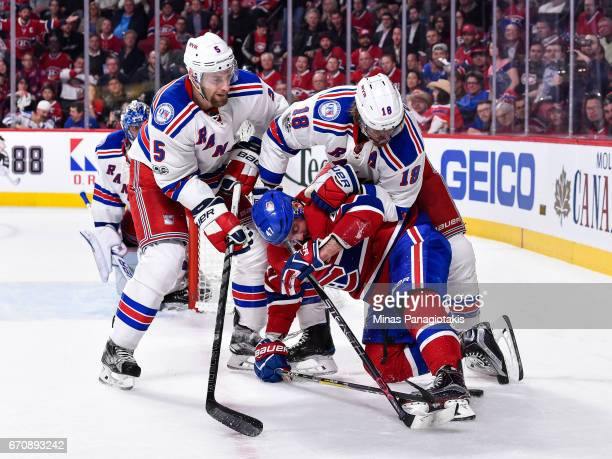 Dan Girardi of the New York Rangers and teammate Marc Staal hold down Alexander Radulov of the Montreal Canadiens in Game Five of the Eastern...