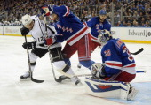 Dan Girardi of the New York Rangers battles with Marian Gaborik of the Los Angeles Kings in front of goaltender Henrik Lundqvist in the first period...