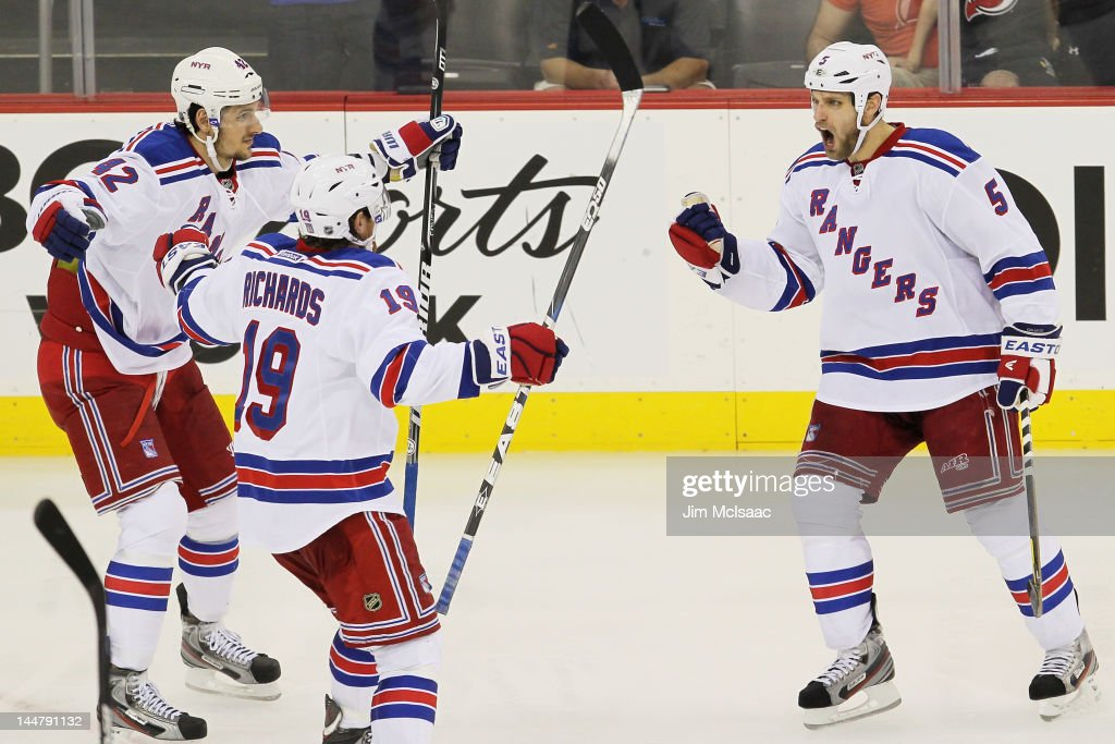 Dan Girardi of the New York Rangers celebrates his third period goal with teammates Brad Richards and Artem Anisimov in Game Three of the Eastern...