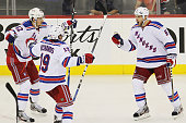 Dan Girardi of the New York Rangers celebrates his third period goal with teammates Brad Richards and Artem Anisimov in Game Three of the Eastern...