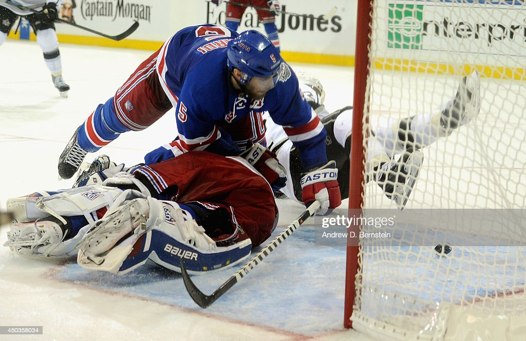 Dan Girardi #5 of the New York Rangers falls over goaltender <a gi-track='captionPersonalityLinkClicked' href=/galleries/search?phrase=Henrik+Lundqvist&family=editorial&specificpeople=217958 ng-click='$event.stopPropagation()'>Henrik Lundqvist</a> #30 to make a save during the third period of Game Three of the 2014 Stanley Cup Final at Madison Square Garden on June 9, 2014 in New York City.