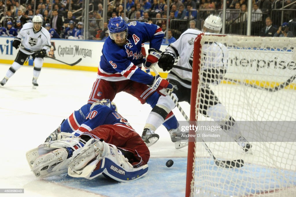 Dan Girardi #5 of the New York Rangers helps goaltender <a gi-track='captionPersonalityLinkClicked' href=/galleries/search?phrase=Henrik+Lundqvist&family=editorial&specificpeople=217958 ng-click='$event.stopPropagation()'>Henrik Lundqvist</a> #30 block a shot during the third period of Game Three of the 2014 Stanley Cup Final at Madison Square Garden on June 9, 2014 in New York City.