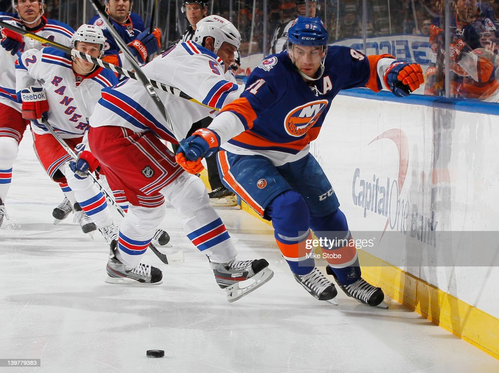 Dan Girardi #5 of the New York Rangers hits <a gi-track='captionPersonalityLinkClicked' href=/galleries/search?phrase=John+Tavares&family=editorial&specificpeople=601791 ng-click='$event.stopPropagation()'>John Tavares</a> #91 of the New York Islanders at Nassau Veterans Memorial Coliseum on February 24, 2012 in Uniondale, New York.