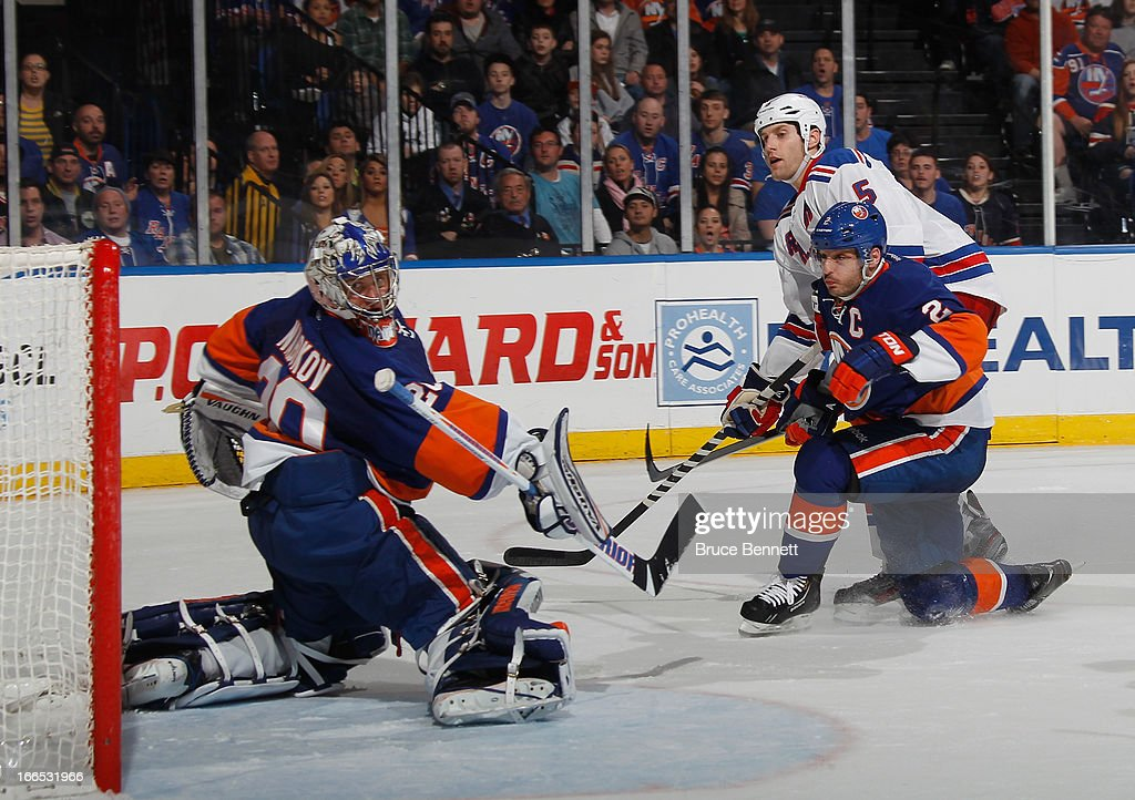 Dan Girardi #5 of the New York Rangers scores the game winning goal at 3:11 of overtime against <a gi-track='captionPersonalityLinkClicked' href=/galleries/search?phrase=Evgeni+Nabokov&family=editorial&specificpeople=171380 ng-click='$event.stopPropagation()'>Evgeni Nabokov</a> #20 of the New York Islanders at the Nassau Veterans Memorial Coliseum on April 13, 2013 in Uniondale, New York. The Rangers defeated the Islanders 1-0 in overtime.