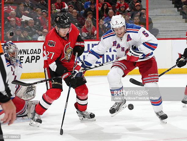 Dan Girardi of the New York Rangers takes a puck off his foot as Curtis Lazar of the Ottawa Senators looks for the rebound during an NHL game at...
