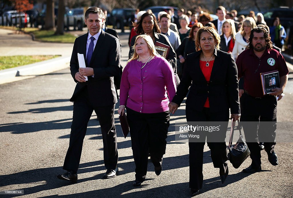 Dan Gross (L), president of the Brady Campaign, arrives with survivors and family members of victims of gun violence at a news conference at the House Triangle on Capitol Hill December 18, 2012 in Washington, DC. U.S. Rep. David Cicilline (D-RI) held a news conference with the Brady Campaign to discuss gun violence.
