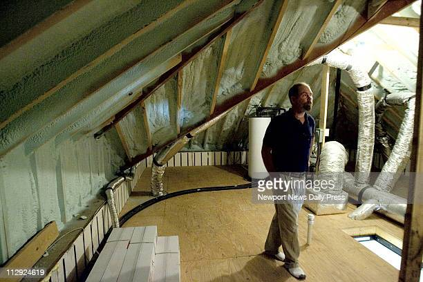 Dan Guinn checks out insulation inside an attic Guinn and his wife built a 'green house' to help their asthmatic daughter her breath better
