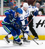Dan Hamhuis of the Vancouver Canucks and Steven Stamkos of the Tampa Bay Lightning battle along the boards during their NHL game at Rogers Arena...