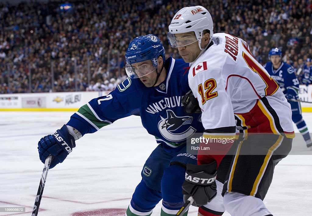 Dan Hamhuis #2 of the Vancouver Canucks battles for position with Jarome Iginla #12 of the Calgary Flames while heading into the corner for the loose puck during the third period of NHL action on January 23, 2013 at Rogers Arena in Vancouver, British Columbia, Canada.