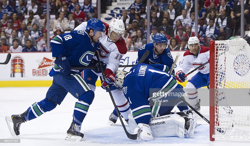 <a gi-track='captionPersonalityLinkClicked' href=/galleries/search?phrase=Dan+Hamhuis&family=editorial&specificpeople=204213 ng-click='$event.stopPropagation()'>Dan Hamhuis</a> #2 of the Vancouver Canucks can't stop the puck from a shot by Max Pacioretty #67 of the Montreal Canadiens (not shown) from crossing the goal line behind goalie <a gi-track='captionPersonalityLinkClicked' href=/galleries/search?phrase=Roberto+Luongo&family=editorial&specificpeople=202638 ng-click='$event.stopPropagation()'>Roberto Luongo</a> #1 of the Vancouver Canucks during the first period in NHL action on October 12, 2013 at Rogers Arena in Vancouver, British Columbia, Canada. <a gi-track='captionPersonalityLinkClicked' href=/galleries/search?phrase=Ryan+Stanton&family=editorial&specificpeople=7184071 ng-click='$event.stopPropagation()'>Ryan Stanton</a> #18 of the Vancouver Canucks ties up <a gi-track='captionPersonalityLinkClicked' href=/galleries/search?phrase=Rene+Bourque&family=editorial&specificpeople=685715 ng-click='$event.stopPropagation()'>Rene Bourque</a> #17 of the Montreal Canadiens as <a gi-track='captionPersonalityLinkClicked' href=/galleries/search?phrase=Francis+Bouillon&family=editorial&specificpeople=215165 ng-click='$event.stopPropagation()'>Francis Bouillon</a> #55 of the Montreal Canadiens look on during the play.