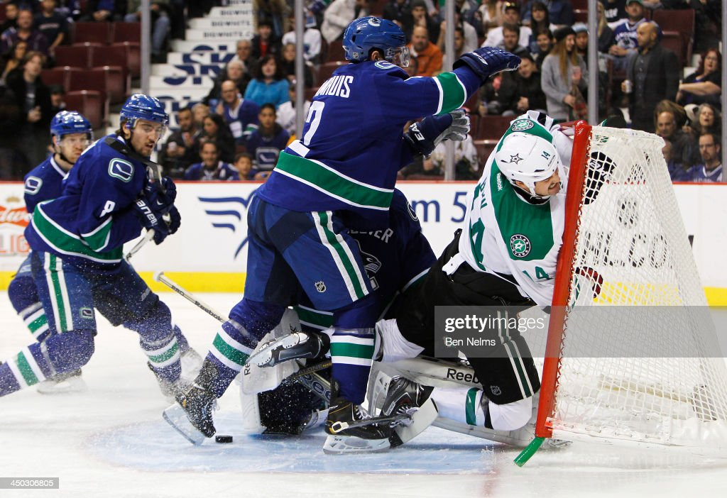 <a gi-track='captionPersonalityLinkClicked' href=/galleries/search?phrase=Dan+Hamhuis&family=editorial&specificpeople=204213 ng-click='$event.stopPropagation()'>Dan Hamhuis</a> #2 of the Vancouver Canucks checks <a gi-track='captionPersonalityLinkClicked' href=/galleries/search?phrase=Jamie+Benn&family=editorial&specificpeople=4595070 ng-click='$event.stopPropagation()'>Jamie Benn</a> #14 of the Dallas Stars into Canucks goaltender <a gi-track='captionPersonalityLinkClicked' href=/galleries/search?phrase=Roberto+Luongo&family=editorial&specificpeople=202638 ng-click='$event.stopPropagation()'>Roberto Luongo</a>'s net during the first period of their NHL game at Rogers Arena on November 17, 2013 in Vancouver, British Columbia, Canada.