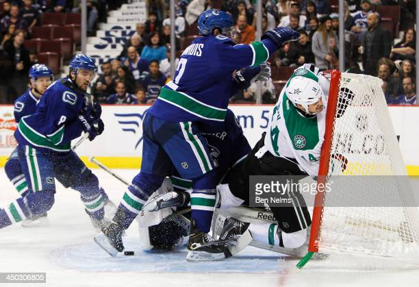 Dan Hamhuis of the Vancouver Canucks checks Jamie Benn of the Dallas Stars into Canucks goaltender Roberto Luongo's net during the first period of...