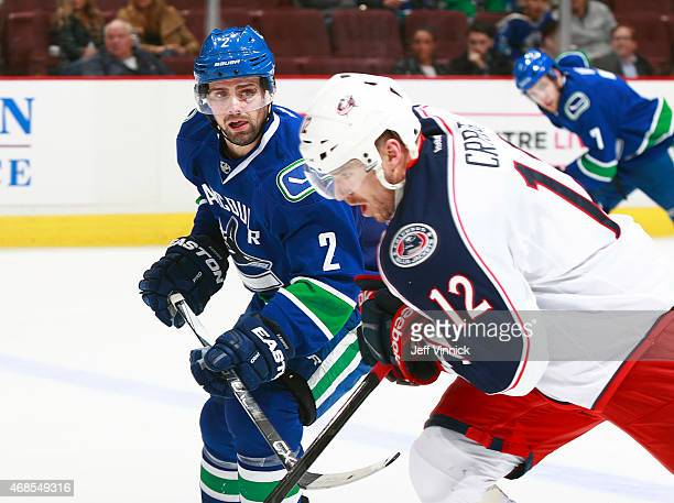 Dan Hamhuis of the Vancouver Canucks checks Ryan Craig of the Columbus Blue Jackets during their NHL game at Rogers Arena March 19 2015 in Vancouver...