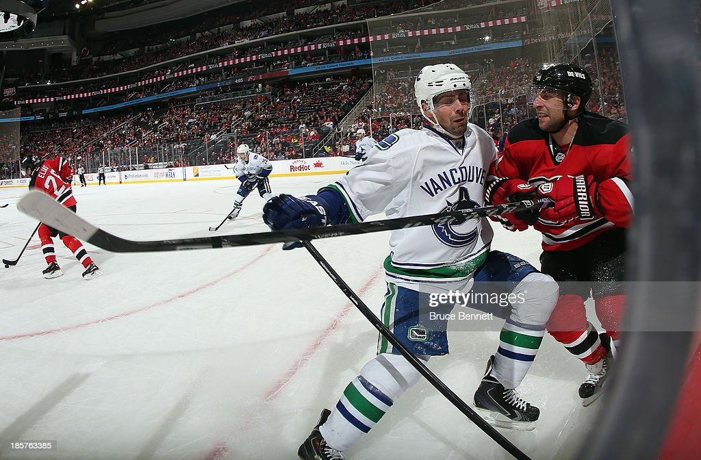<a gi-track='captionPersonalityLinkClicked' href=/galleries/search?phrase=Dan+Hamhuis&family=editorial&specificpeople=204213 ng-click='$event.stopPropagation()'>Dan Hamhuis</a> #2 of the Vancouver Canucks checks <a gi-track='captionPersonalityLinkClicked' href=/galleries/search?phrase=Stephen+Gionta&family=editorial&specificpeople=817969 ng-click='$event.stopPropagation()'>Stephen Gionta</a> #11 of the New Jersey Devils into the boards at the Prudential Center on October 24, 2013 in Newark, New Jersey.