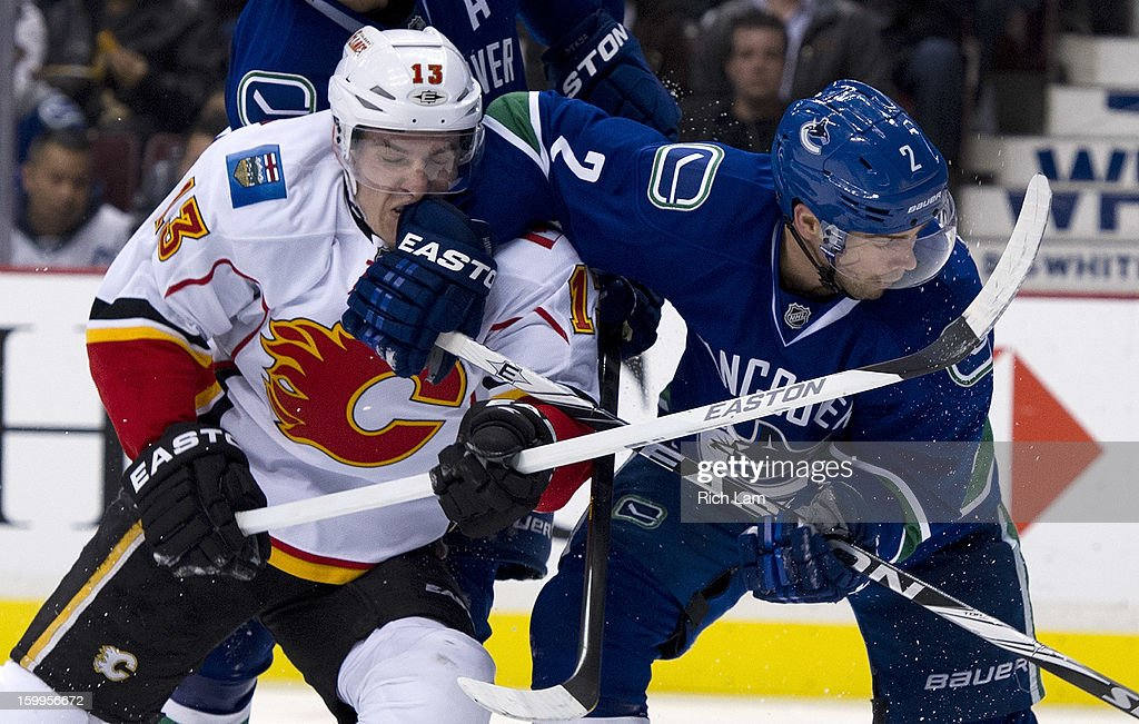Dan Hamhuis #2 of the Vancouver Canucks hits TJ Brodie #13 of the Calgary Flames in the face as they battle for position in front of the net during the third period of NHL action on January 23, 2013 at Rogers Arena in Vancouver, British Columbia, Canada.