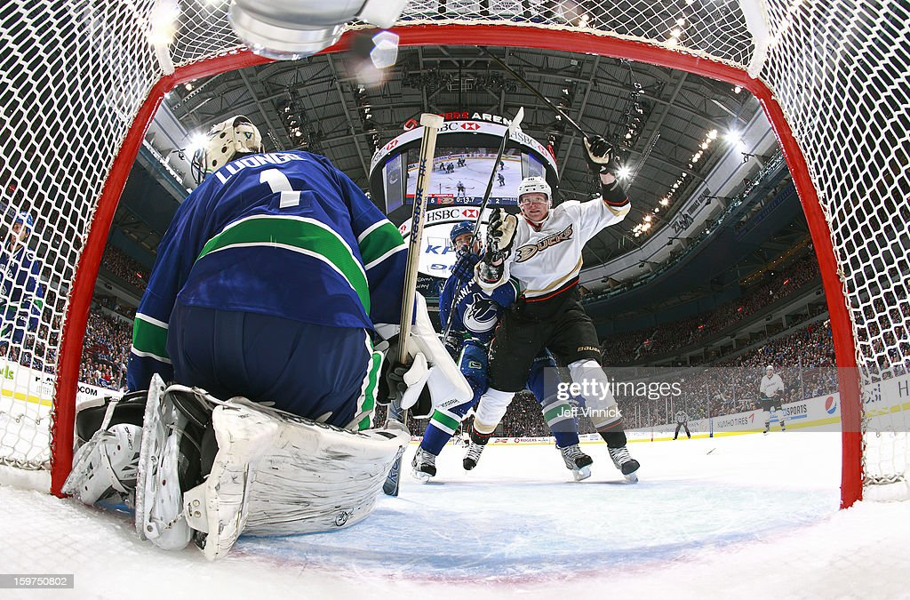 Dan Hamhuis #2 of the Vancouver Canucks looks on as Corey Perry #10 of the Anaheim Ducks celebrates an Anaheim goal against Roberto Luongo #1 of the Vancouver Canucks during their season-opening NHL game at Rogers Arena January 19, 2013 in Vancouver, British Columbia, Canada. Anaheim won 7-3.