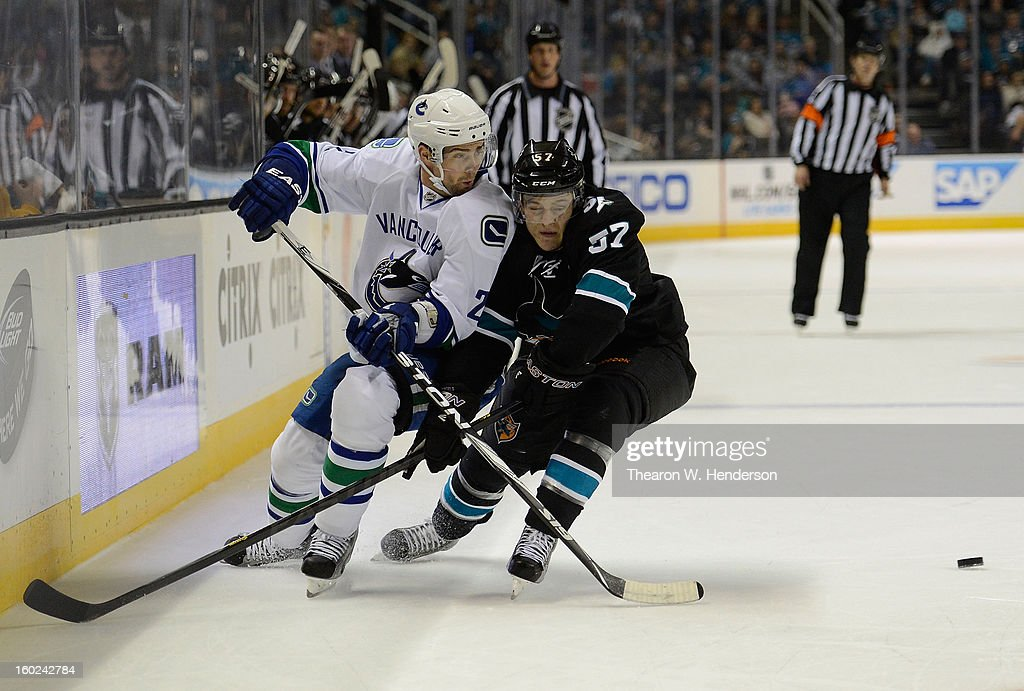 Dan Hamhuis #2 of the Vancouver Canucks passed the puck past Tommy Wingels #57 of the San Jose Sharks in the first period of their game at HP Pavilion on January 27, 2013 in San Jose, California.