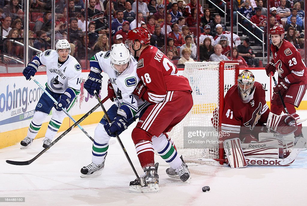 <a gi-track='captionPersonalityLinkClicked' href=/galleries/search?phrase=Dan+Hamhuis&family=editorial&specificpeople=204213 ng-click='$event.stopPropagation()'>Dan Hamhuis</a> #2 of the Vancouver Canucks passes the puck past <a gi-track='captionPersonalityLinkClicked' href=/galleries/search?phrase=Lauri+Korpikoski&family=editorial&specificpeople=2108074 ng-click='$event.stopPropagation()'>Lauri Korpikoski</a> #28 and goaltender Mike Smith #41 of the Phoenix Coyotes during the NHL game at Jobing.com Arena on March 21, 2013 in Glendale, Arizona. The Canucks defeated the Coyotes 2-1.