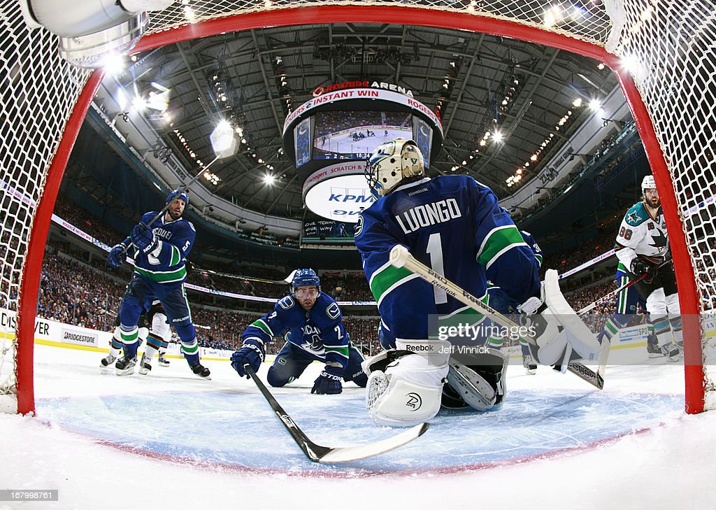 <a gi-track='captionPersonalityLinkClicked' href=/galleries/search?phrase=Dan+Hamhuis&family=editorial&specificpeople=204213 ng-click='$event.stopPropagation()'>Dan Hamhuis</a> #2 of the Vancouver Canucks reaches behind <a gi-track='captionPersonalityLinkClicked' href=/galleries/search?phrase=Roberto+Luongo&family=editorial&specificpeople=202638 ng-click='$event.stopPropagation()'>Roberto Luongo</a> #1 of the Canucks to prevent a goal against the San Jose Sharks during Game Two of the Western Conference Quarterfinals during the 2013 NHL Stanley Cup Playoffs at Rogers Arena on May 3, 2013 in Vancouver, British Columbia, Canada. San Jose won 3-2 in overtime.