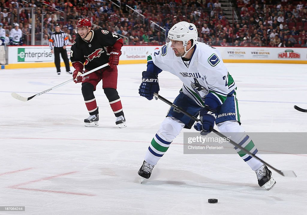 <a gi-track='captionPersonalityLinkClicked' href=/galleries/search?phrase=Dan+Hamhuis&family=editorial&specificpeople=204213 ng-click='$event.stopPropagation()'>Dan Hamhuis</a> #2 of the Vancouver Canucks shoots the puck ahead of <a gi-track='captionPersonalityLinkClicked' href=/galleries/search?phrase=Radim+Vrbata&family=editorial&specificpeople=204716 ng-click='$event.stopPropagation()'>Radim Vrbata</a> #17 of the Phoenix Coyotes during the NHL game at Jobing.com Arena on November 5, 2013 in Glendale, Arizona. The Coyotes defeated the Canucks 3-2 in an overtime shoot out.