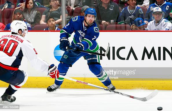 Dan Hamhuis of the Vancouver Canucks shoots the puck past Marcus Johansson of the Washington Capitals during their NHL game at Rogers Arena October...