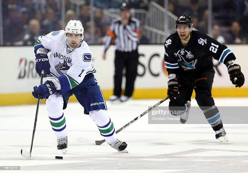 Dan Hamhuis #2 of the Vancouver Canucks skates with the puck ahead of T.J. Galiardi #21 of the San Jose Sharks in Game Three of the Western Conference Quarterfinals during the 2013 NHL Stanley Cup Playoffs at HP Pavilion on May 5, 2013 in San Jose, California. The Sharks defeated the Canucks 5-2.