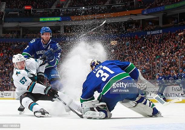 Dan Hamhuis watches Eddie Lack of the Vancouver Canucks make a save on Tommy Wingels of the San Jose Sharks during their NHL game at Rogers Arena...