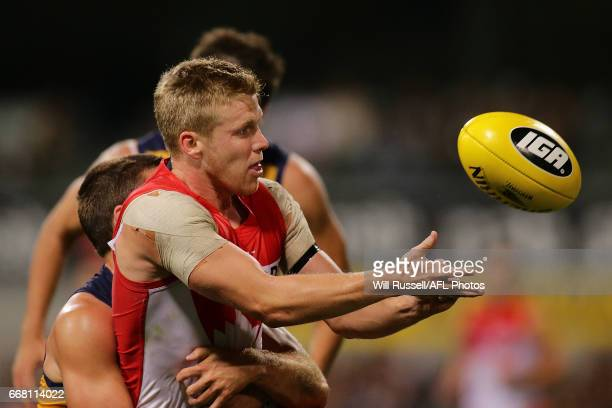 Dan Hannebery of the Swans handballs under pressure from Jamie Cripps of the Eagles during the round four AFL match between the West Coast Eagles and...