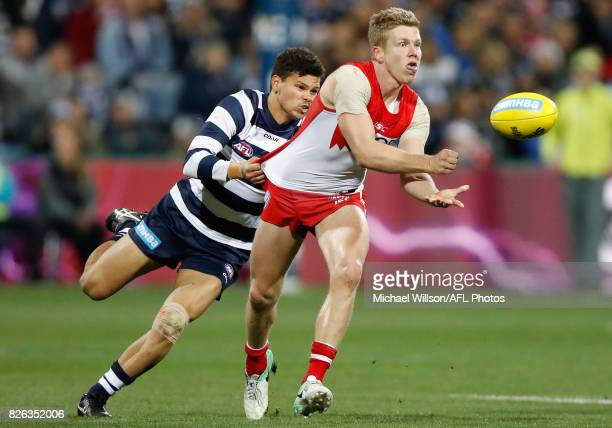 Dan Hannebery of the Swans is tackled by Brandan Parfitt of the Cats during the 2017 AFL round 20 match between the Geelong Cats and the Sydney Swans...