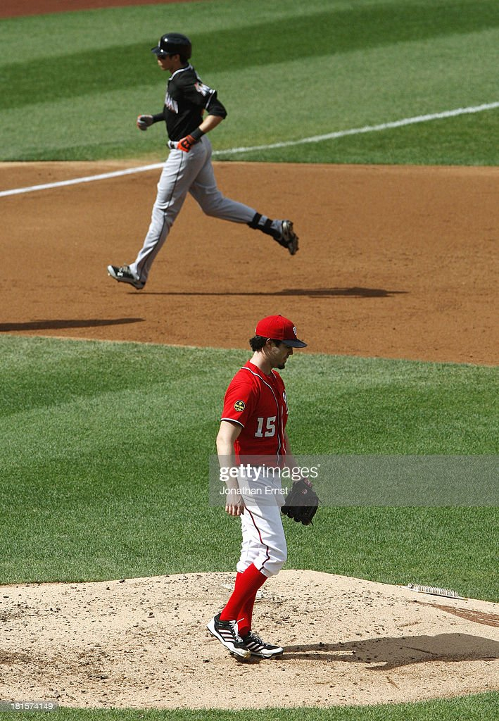 Dan Haren #15 (BOTTOM) of the Washington Nationals stands on the mound as Christian Yelich #21 (TOP) of the Miami Marlins runs the bases after his solo home run during the third inning of game 1 of their day-night doubleheader at Nationals Park on September 22, 2013 in Washington, DC. The Marlins won the game, 4-2.