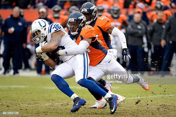 Dan Herron of the Indianapolis Colts is tackled by Brandon Marshall of the Denver Broncos during a 2015 AFC Divisional Playoff game at Sports...