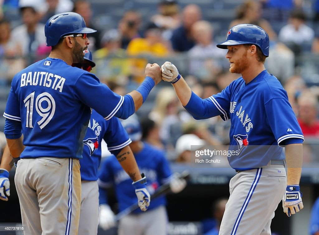 Dan Johnson #16 of the Toronto Blue Jays is congratulated by teammate Jose Bautista #19 after Johnson hit a three-run home run in the ninth inning against the New York Yankees during a MLB baseball game at Yankee Stadium on July 26, 2014 in the Bronx borough of New York City. The Blue Jays defeated the Yankees 6-4.