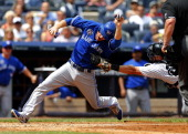 Dan Johnson of the Toronto Blue Jays is tagged out by catcher Francisco Cervelli of the New York Yankees on a throw from right fielder Zelous Wheeler...