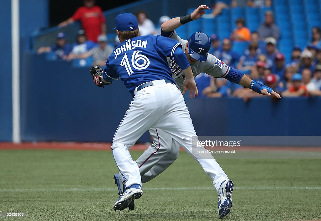 Dan Johnson #16 of the Toronto Blue Jays tags out Daniel Robertson #19 of the Texas Rangers in a run-down between first base and second base to end the sixth inning during MLB game action on July 20, 2014 at Rogers Centre in Toronto, Ontario, Canada.