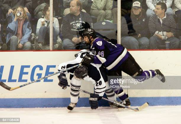 Dan Krmpotich of the University of St Thomas checks Brett Shirreffs of Middlebury College into the wall during the Division III Men's Ice Hockey...