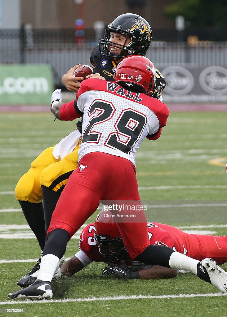 Dan LeFevour of the Hamilton TigerCats is stopped by Jamar Wall of the Calgary Stampeders in a CFL game at Ron Joyce Stadium on August 16 2014 in...