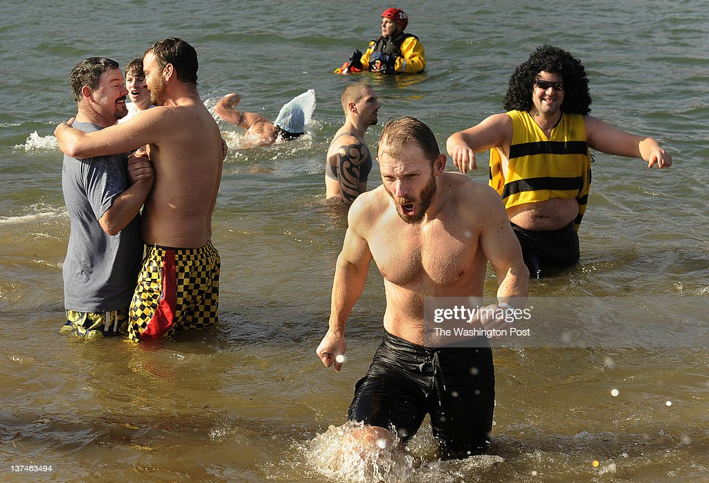 Dan Mills, center right, of Frederick, MD rushes out of the Potomac River as he and others take part in the Williamsport Polar Bear Plunge presented by the Humane Society of Washington County on Sunday January 01, 2012 at River Bottom Park in Williamsport, MD. Wearing a full range of outfits, people welcomed the New Year with a plunge into the Potomac River during the annual event.