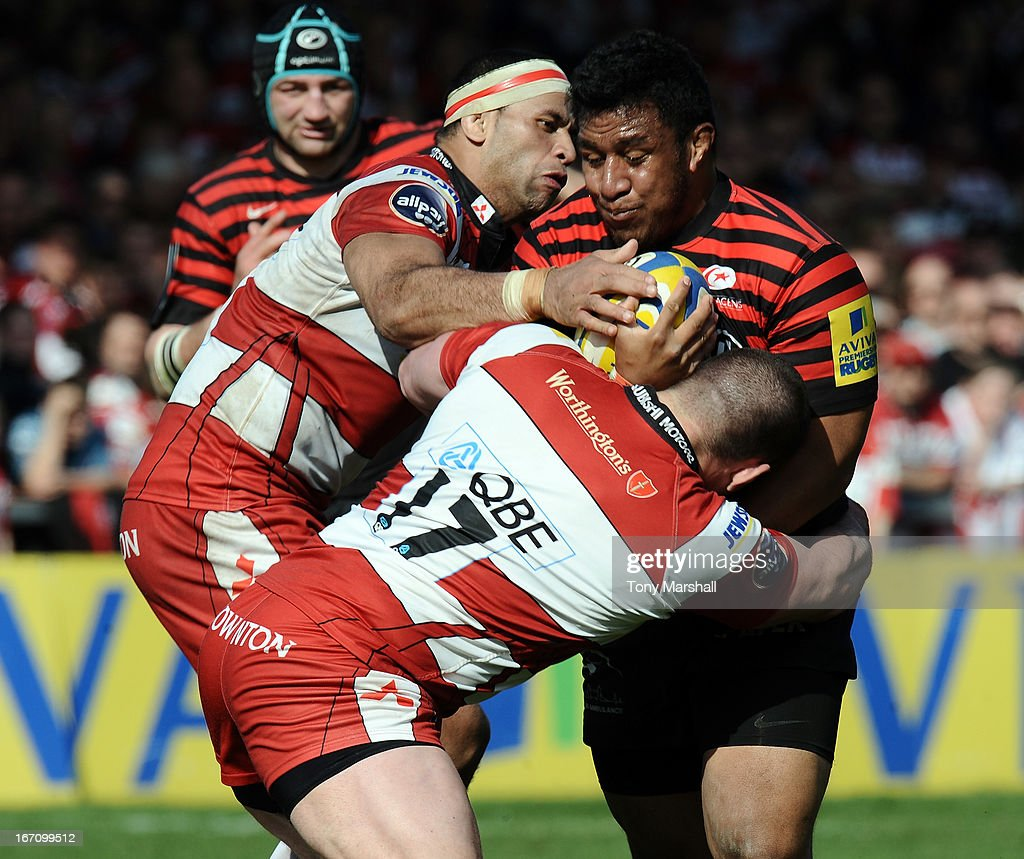 Dan Murphy (17) and Lua Lokotui of Gloucester tackle Mako Vunipola of Saracens during the Aviva Premiership match between Gloucester and Saracens at Kingsholm Stadium on April 20, 2013 in Gloucester, England.