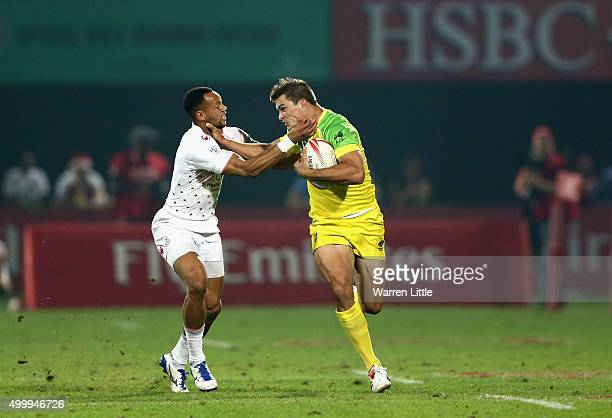 Dan Norton of England and Ed Jenkins of Australia hand each other off during the Emirates Dubai Rugby Sevens HSBC World Rugby Sevens Series at The...