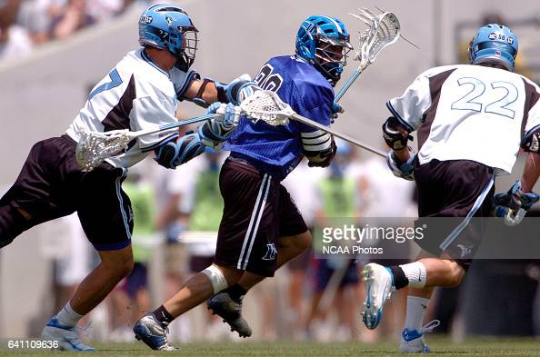 Dan Oppedisano of Duke gains possession of a face off and tries to work his way around Lou Braun and Brendan Skakandi of Johns Hopkins during the...
