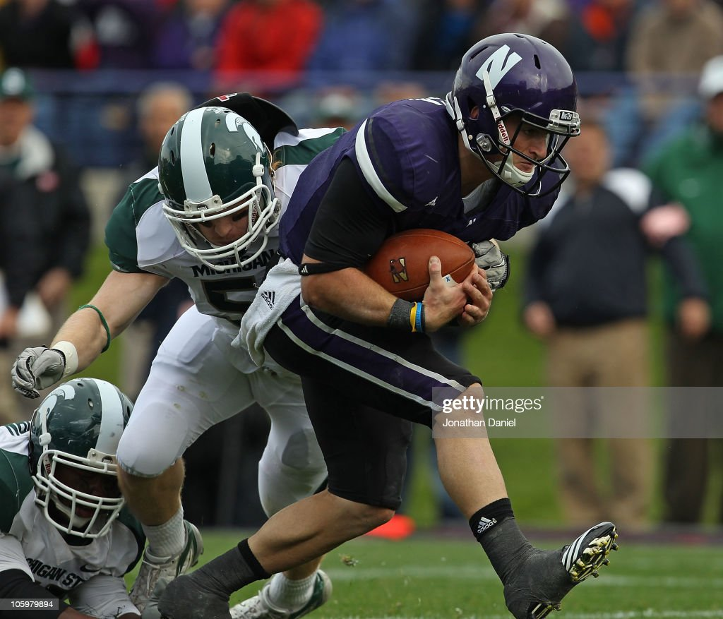 Dan Persa #7 of the Northwestern Wildcats runs past Eric Gordon #43 of the Michigan State Spartans for a touchdown at Ryan Field on October 23, 2010 in Evanston, Illinois. Michigan State defeated Northwestern 35-27.