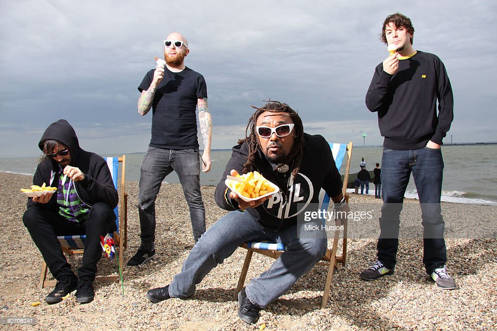 Dan Pugsley, Mikey Demus, Benji Webbeand Arya Goggin of Skindred pose for a group portrait session on the beach eating chips and ice creams on July 18th, 2009 in Southend, Essex.