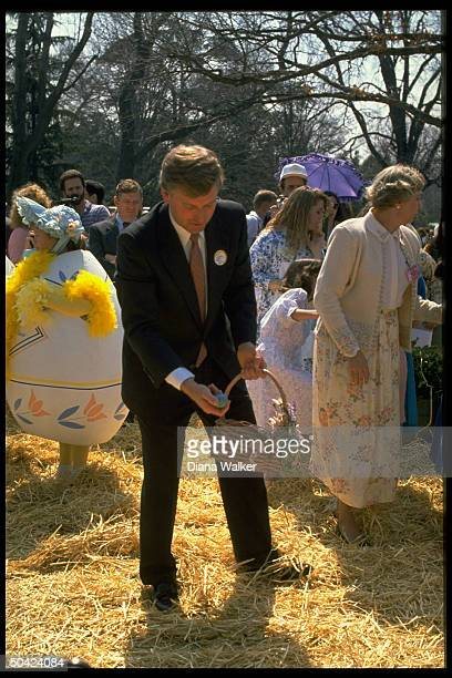 VP Dan Quayle poised w basket hiding egg at WH Easter egg hunt w bonnet eggcostumed girls et al in bkgrd