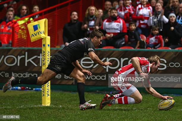Dan Robson of Gloucester scores his sides opening try despite the attentions of Richard Wigglesworth of Saracens during the Aviva Premiership match...