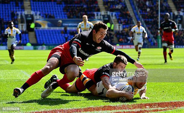 Dan Robson of Wasps dives over for his side's first try under pressure from Richard Wigglesworth of Saracens and Alex Goode of Saracens during the...