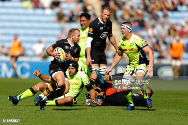 Dan Robson of Wasps runs with the ball ahead of Ben Curry of Sale Sharks during the Aviva Premiership match between Wasps and Sale Sharks at The...