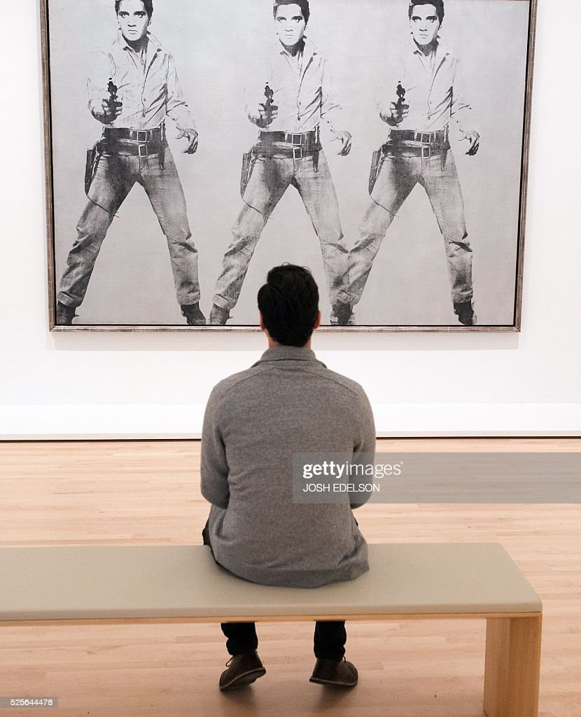 Dan Rosenbaum looks at an art piece entitled 'Triple Elvis' by Andy Warhol inside the San Francisco Museum of Modern Art (SFMOMA) in San Francisco, California on April 28, 2016. The newly redesigned museum integrates a 10-story expansion in a new building and will open to the public on May 14, 2016. / AFP / Josh Edelson / RESTRICTED